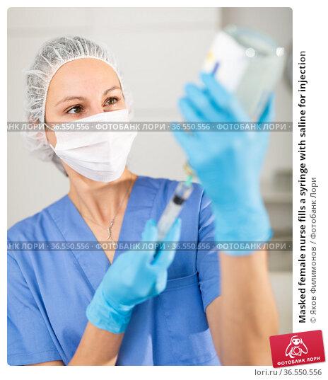 Masked female nurse fills a syringe with saline for injection. Стоковое фото, фотограф Яков Филимонов / Фотобанк Лори