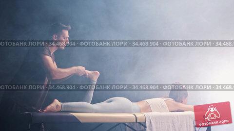 Massage session in the black smoky studio - man therapist massaging young woman's foot. Стоковое видео, видеограф Константин Шишкин / Фотобанк Лори