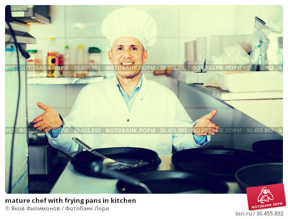 mature chef with frying pans in kitchen. Стоковое фото, фотограф Яков Филимонов / Фотобанк Лори