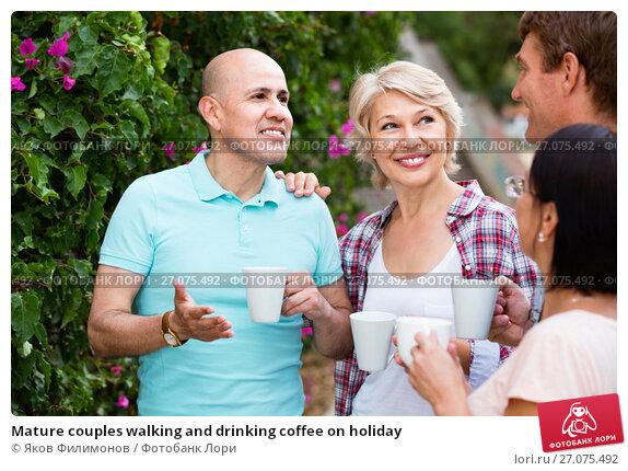 Купить «Mature couples walking and drinking coffee on holiday», фото № 27075492, снято 25 июля 2017 г. (c) Яков Филимонов / Фотобанк Лори