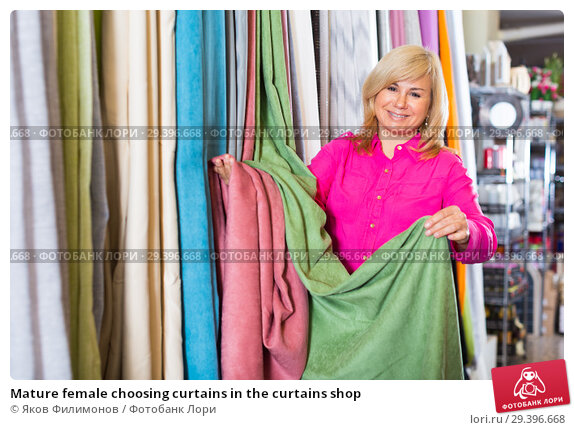 Купить «Mature female choosing curtains in the curtains shop», фото № 29396668, снято 17 января 2018 г. (c) Яков Филимонов / Фотобанк Лори