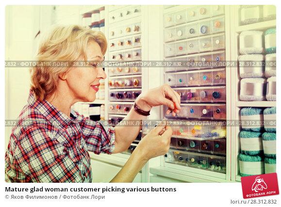 Купить «Mature glad woman customer picking various buttons», фото № 28312832, снято 22 мая 2019 г. (c) Яков Филимонов / Фотобанк Лори