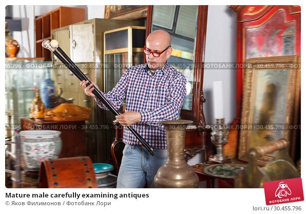 Mature male carefully examining antiques. Стоковое фото, фотограф Яков Филимонов / Фотобанк Лори
