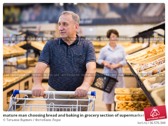 mature man choosing bread and baking in grocery section of supermarket. Стоковое фото, фотограф Татьяна Яцевич / Фотобанк Лори