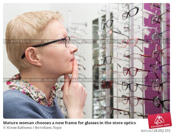 Купить «Mature woman chooses a new frame for glasses in the store optics», фото № 28052372, снято 13 февраля 2018 г. (c) Юлия Бабкина / Фотобанк Лори