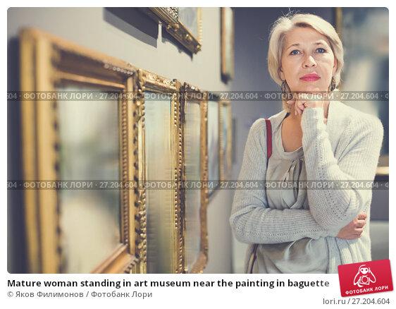 Купить «Mature woman standing in art museum near the painting in baguette», фото № 27204604, снято 7 октября 2017 г. (c) Яков Филимонов / Фотобанк Лори