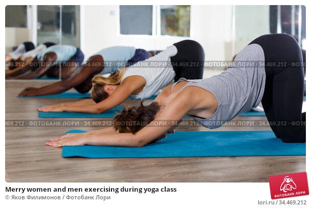 Merry women and men exercising during yoga class. Стоковое фото, фотограф Яков Филимонов / Фотобанк Лори