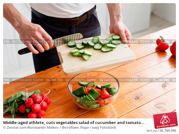 Middle-aged athlete, cuts vegetables salad of cucumber and tomato... Стоковое фото, фотограф Zoonar.com/Konstantin Malkov / easy Fotostock / Фотобанк Лори