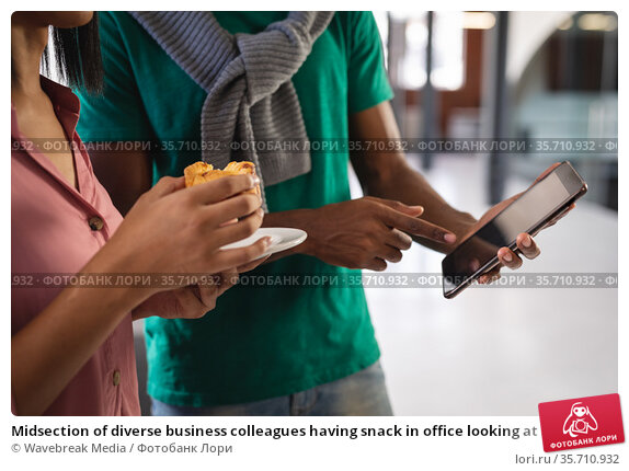 Midsection of diverse business colleagues having snack in office looking at smartphone. Стоковое фото, агентство Wavebreak Media / Фотобанк Лори