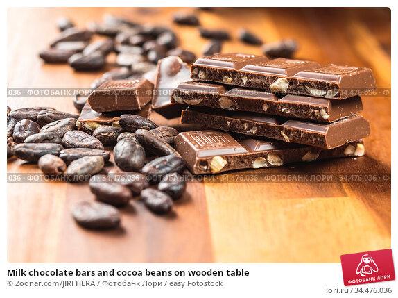 Milk chocolate bars and cocoa beans on wooden table. Стоковое фото, фотограф Zoonar.com/JIRI HERA / easy Fotostock / Фотобанк Лори