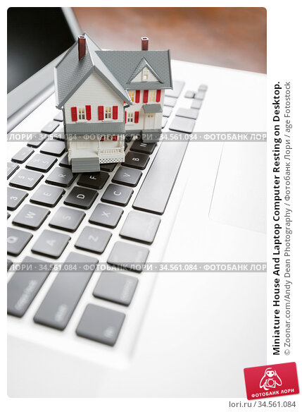 Miniature House And Laptop Computer Resting on Desktop. Стоковое фото, фотограф Zoonar.com/Andy Dean Photography / age Fotostock / Фотобанк Лори