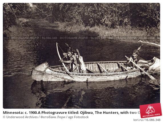 MInnesota: c. 1900.A Photogravure titled: Ojibwa, The Hunters, with two Ojibwas hunting from a birchbark canoe. Редакционное фото, фотограф Underwood Archives / age Fotostock / Фотобанк Лори
