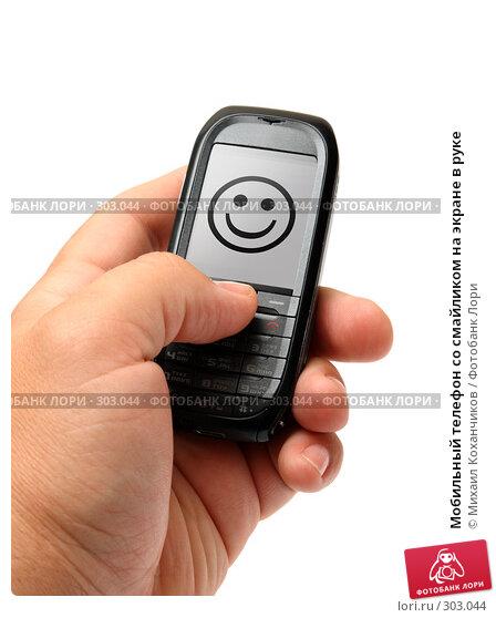 Мобильный телефон со смайликом на экране в руке, фото № 303044, снято 28 мая 2008 г. (c) Михаил Коханчиков / Фотобанк Лори