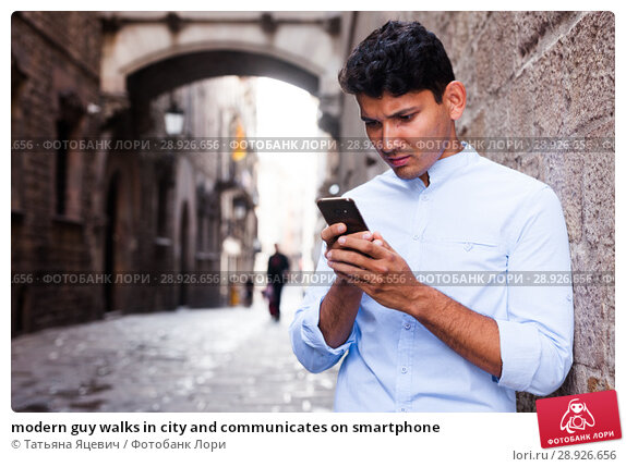 Купить «modern guy walks in city and communicates on smartphone», фото № 28926656, снято 25 июля 2018 г. (c) Татьяна Яцевич / Фотобанк Лори