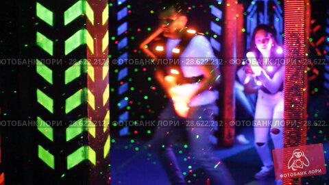 Купить «Modern young people with laser pistols playing laser tag on dark labyrinth», видеоролик № 28622212, снято 22 мая 2018 г. (c) Яков Филимонов / Фотобанк Лори