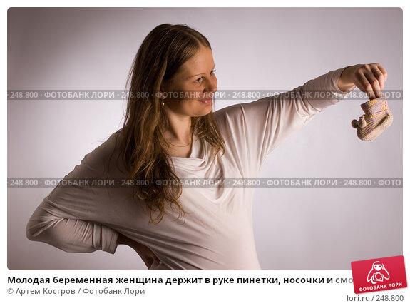 Молодая беременная женщина держит в руке пинетки, носочки и смотрит на них, фото № 248800, снято 4 апреля 2008 г. (c) Артем Костров / Фотобанк Лори
