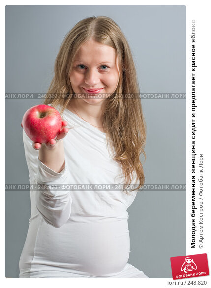 Молодая беременная женщина сидит и предлагает красное яблоко, фото № 248820, снято 4 апреля 2008 г. (c) Артем Костров / Фотобанк Лори