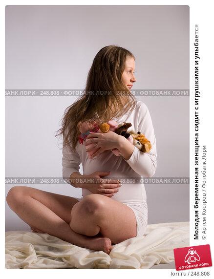 Молодая беременная женщина сидит с игрушками и улыбается, фото № 248808, снято 4 апреля 2008 г. (c) Артем Костров / Фотобанк Лори