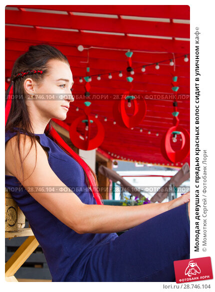 Купить «Молодая девушка с прядью красных волос сидит в уличном кафе», фото № 28746104, снято 12 июля 2018 г. (c) Момотюк Сергей / Фотобанк Лори