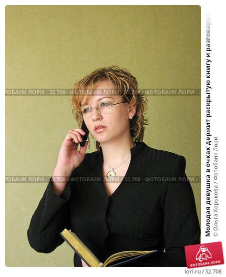 Молодая девушка в очках держит раскрытую книгу и разговаривает по телефону. Обеспокоенное выражение лица., фото № 32708, снято 12 апреля 2007 г. (c) Ольга Хорькова / Фотобанк Лори