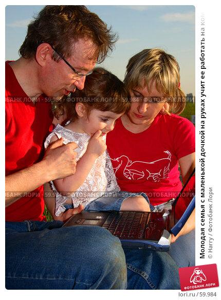 Молодая семья с маленькой дочкой на руках учит ее работать на компьютере в лучах закатного солнца. Сценка на природе, ближе  к вечеру., фото № 59984, снято 22 мая 2006 г. (c) Harry / Фотобанк Лори