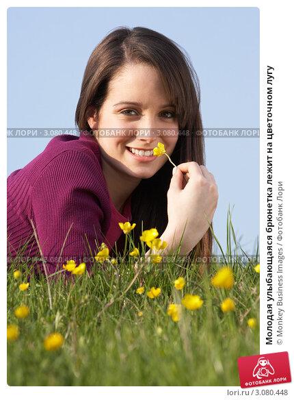 Молодая улыбающаяся брюнетка лежит на цветочном лугу. Стоковое фото, фотограф Monkey Business Images / Фотобанк Лори