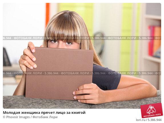 Купить «Молодая женщина прячет лицо за книгой», фото № 5386944, снято 1 июля 2010 г. (c) Phovoir Images / Фотобанк Лори