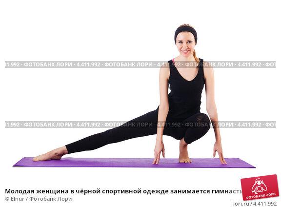 Купить «Молодая женщина в чёрной спортивной одежде занимается гимнастикой на белом фоне», фото № 4411992, снято 17 ноября 2012 г. (c) Elnur / Фотобанк Лори