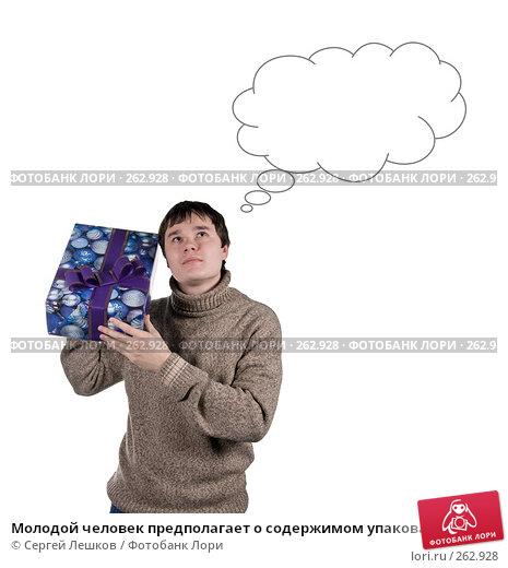 Молодой человек предполагает о содержимом упакованного подарка, фото № 262928, снято 25 ноября 2007 г. (c) Сергей Лешков / Фотобанк Лори