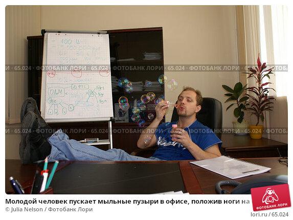 Молодой человек пускает мыльные пузыри в офисе, положив ноги на стол, фото № 65024, снято 22 июля 2007 г. (c) Julia Nelson / Фотобанк Лори