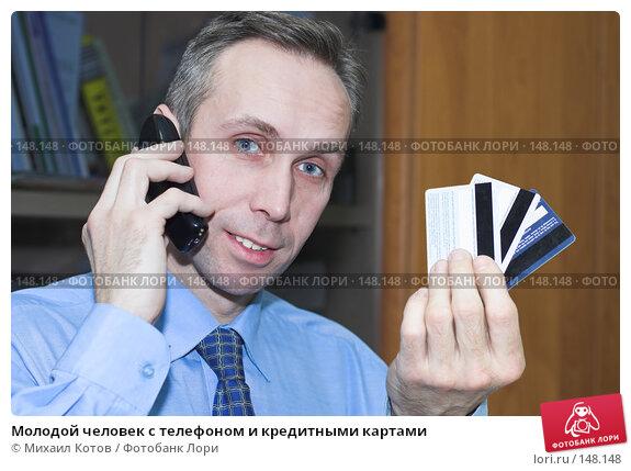 Молодой человек с телефоном и кредитными картами, фото № 148148, снято 24 марта 2017 г. (c) Михаил Котов / Фотобанк Лори