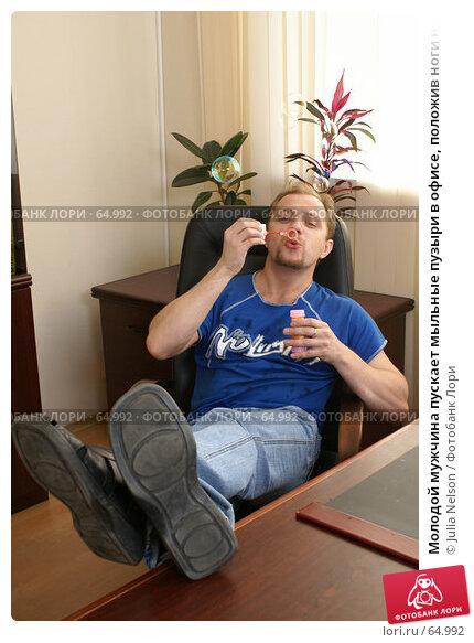 Молодой мужчина пускает мыльные пузыри в офисе, положив ноги на стол, фото № 64992, снято 22 июля 2007 г. (c) Julia Nelson / Фотобанк Лори