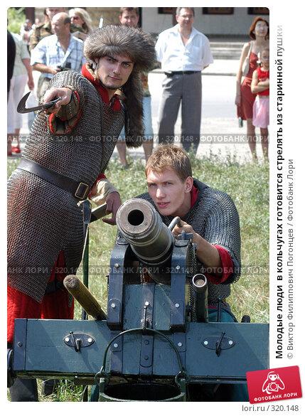 Купить «Молодые люди  в кольчугах готовится стрелять из старинной пушки», фото № 320148, снято 7 августа 2005 г. (c) Виктор Филиппович Погонцев / Фотобанк Лори