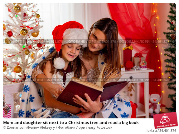 Mom and daughter sit next to a Christmas tree and read a big book. Стоковое фото, фотограф Zoonar.com/Ivanov Aleksey y / easy Fotostock / Фотобанк Лори
