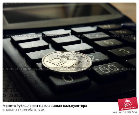 Монета Рубль лежит на клавишах калькулятора. Стоковое фото, фотограф Татьяна Т / Фотобанк Лори