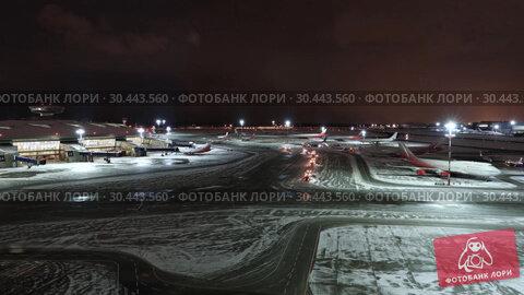 Купить «MOSCOW, RUSSIA - 25 december 2017: Night panoramic view of Terminal A of Vnukovo International Airport and airport building with teletraps and apron with airplanes», видеоролик № 30443560, снято 24 марта 2019 г. (c) Mikhail Starodubov / Фотобанк Лори