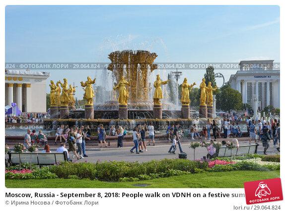 Купить «Moscow, Russia - September 8, 2018: People walk on VDNH on a festive summer day on the background of the fountain of Friendship of  nations», фото № 29064824, снято 8 сентября 2018 г. (c) Ирина Носова / Фотобанк Лори