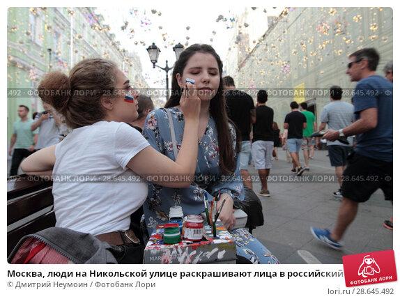 Купить «Москва, люди на Никольской улице раскрашивают лица в российский флаг», эксклюзивное фото № 28645492, снято 23 июня 2018 г. (c) Дмитрий Неумоин / Фотобанк Лори