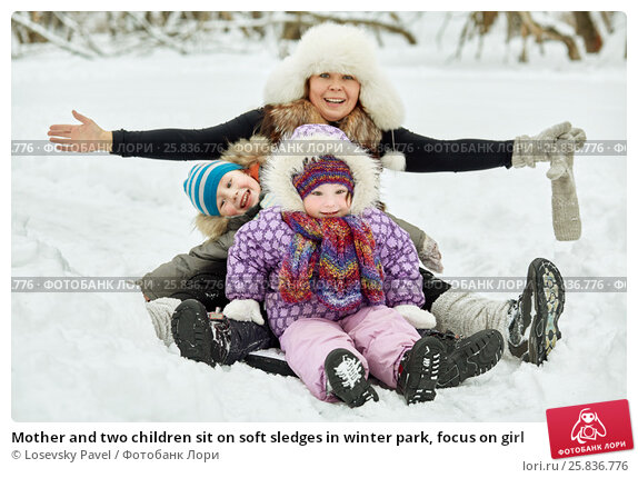 Купить «Mother and two children sit on soft sledges in winter park, focus on girl», фото № 25836776, снято 25 января 2015 г. (c) Losevsky Pavel / Фотобанк Лори