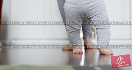 Купить «Mother assisting in her baby first steps», видеоролик № 30295348, снято 12 марта 2019 г. (c) Константин Колосов / Фотобанк Лори