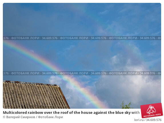 Multicolored rainbow over the roof of the house against the blue sky with clouds. Стоковое фото, фотограф Валерий Смирнов / Фотобанк Лори