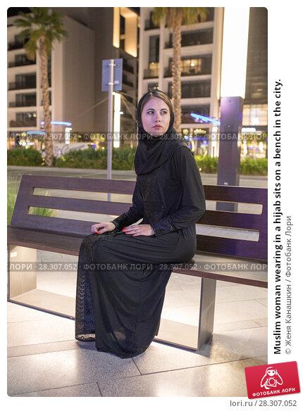 Купить «Muslim woman wearing in a hijab sits on a bench in the city.», фото № 28307052, снято 25 марта 2018 г. (c) Женя Канашкин / Фотобанк Лори