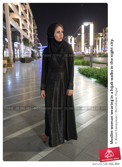 Купить «Muslim woman wearing in a hijab walks in the night city.», фото № 28306480, снято 25 марта 2018 г. (c) Женя Канашкин / Фотобанк Лори