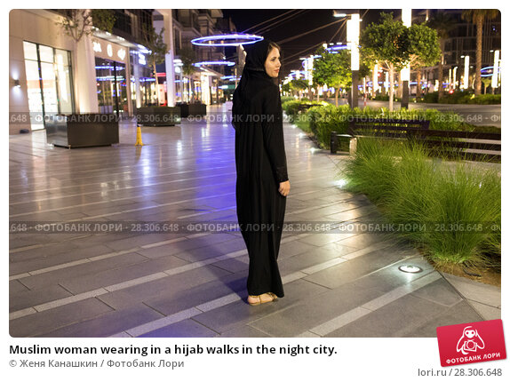 Купить «Muslim woman wearing in a hijab walks in the night city.», фото № 28306648, снято 25 марта 2018 г. (c) Женя Канашкин / Фотобанк Лори