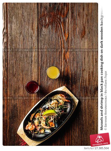 Купить «Mussels and shrimp in black pan cooking dish on dark wooden background», фото № 27385504, снято 11 ноября 2016 г. (c) Евгения Филимонова / Фотобанк Лори
