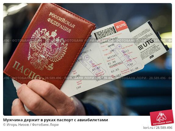 Купить «Мужчина держит в руках паспорт с авиабилетами», эксклюзивное фото № 28589496, снято 1 июня 2018 г. (c) Игорь Низов / Фотобанк Лори