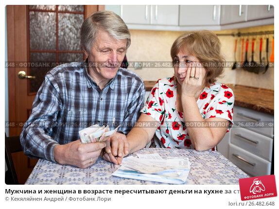 Купить «Мужчина и женщина в возрасте пересчитывают деньги на кухне за столом», фото № 26482648, снято 6 ноября 2016 г. (c) Кекяляйнен Андрей / Фотобанк Лори