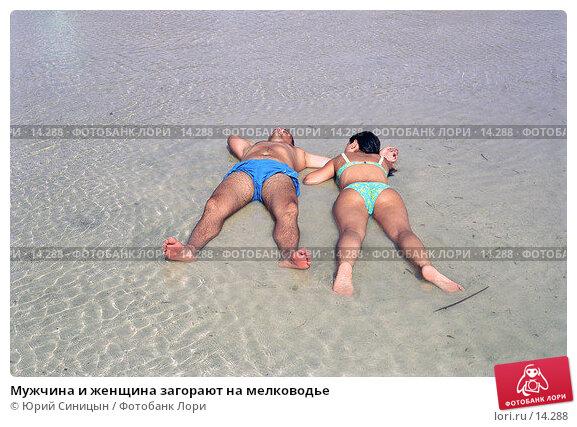 Мужчина и женщина загорают на мелководье, фото № 14288, снято 28 июля 2017 г. (c) Юрий Синицын / Фотобанк Лори