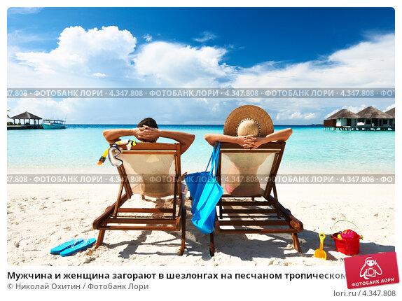 Купить «Мужчина и женщина загорают в шезлонгах на песчаном тропическом пляже. Отпуск», фото № 4347808, снято 11 декабря 2012 г. (c) Николай Охитин / Фотобанк Лори