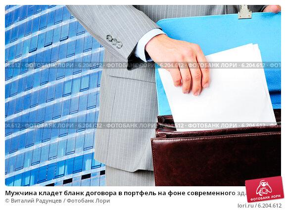 Мужчина кладет бланк договора в портфель на фоне современного здания, фото № 6204612, снято 16 августа 2017 г. (c) Виталий Радунцев / Фотобанк Лори